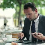 stock-footage-businessman-working-with-tablet-and-smartphone-in-cafe